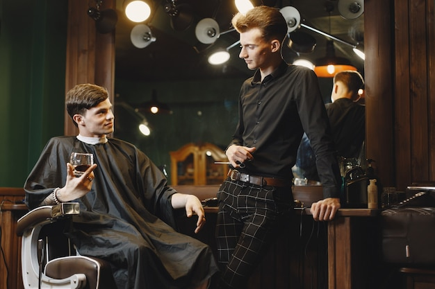 Man sitting in a chair. hairdresser with a client. guy drinkig a whiskey.