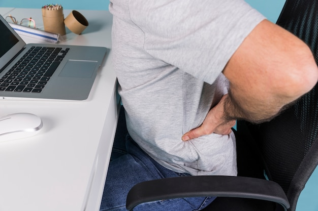 Man sitting in chair suffering from backache while working on laptop