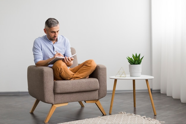 Man sitting on chair and writing on his agenda