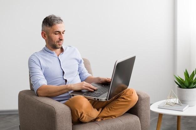 Equipaggi la seduta sulla sedia e la scrittura sul suo computer portatile