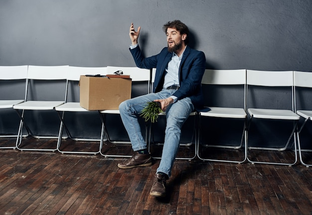Man sitting on chairs with a box job search