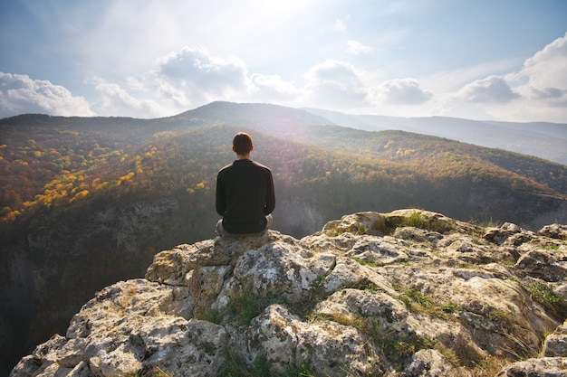Man sitting on the cliff of mountain.