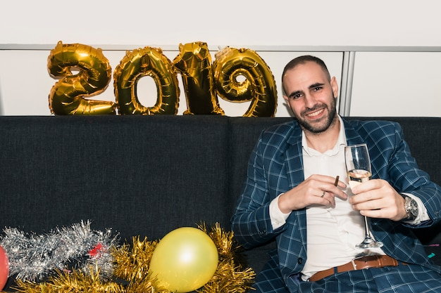 Man sitting on couch with champagne glass