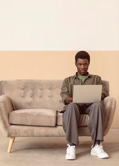 Uomo seduto sul divano e lavora