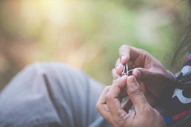 Man sitting to cut nails.