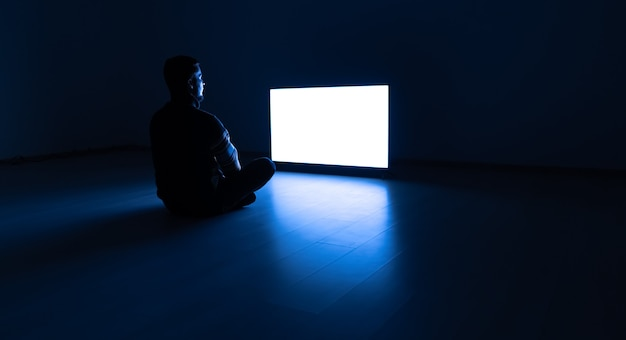 The man sitting in the dark room in front of a television