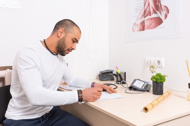 Man sitting at a desk writing notes in an office