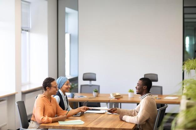 彼の雇用主と机でオフィスの就職の面接のために座っている男 無料写真