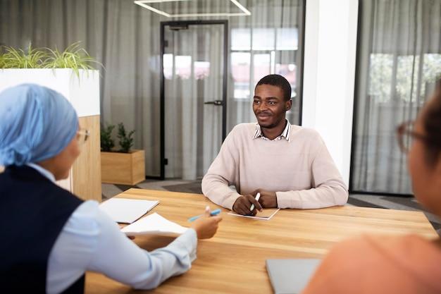 彼の雇用主と机でオフィスの就職の面接のために座っている男