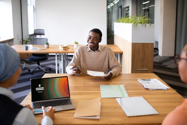 Man sitting down for an office job interview at desk with his employers