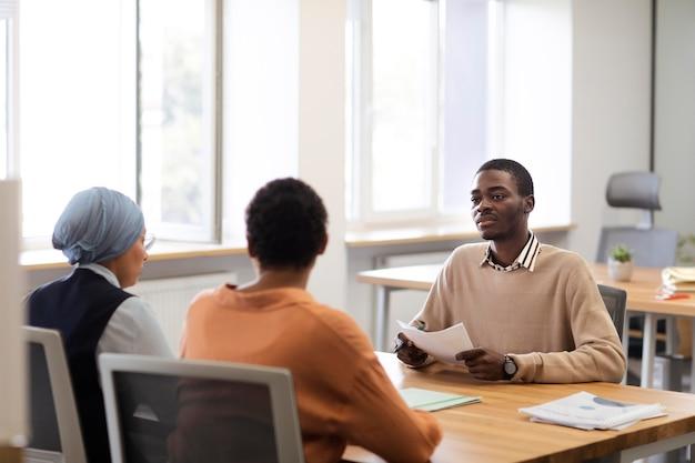 Uomo seduto per un colloquio di lavoro in ufficio alla scrivania con i suoi datori di lavoro