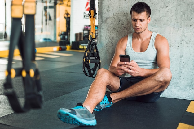 Man sitting on floor using mobile phone in gym
