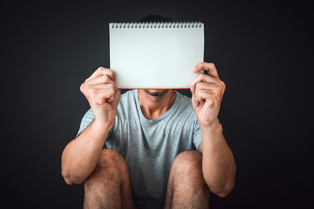 Man sitting on the floor with blank notebook