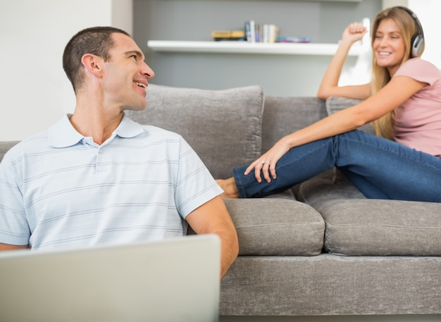 Man sitting on floor with laptop with woman listening to music on the sofa