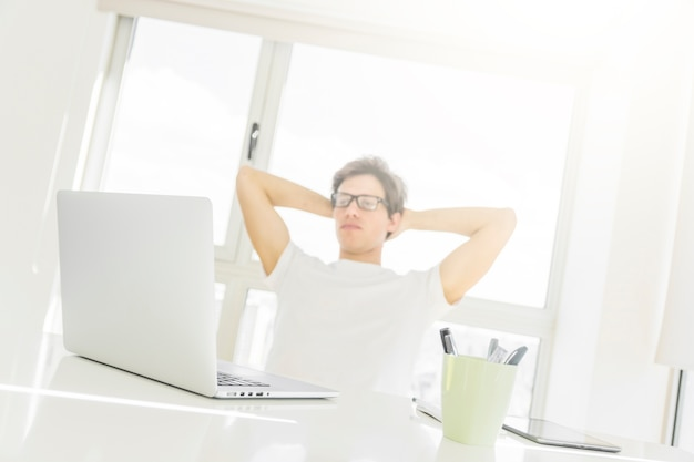 Man sitting in front of laptop with hands behind head