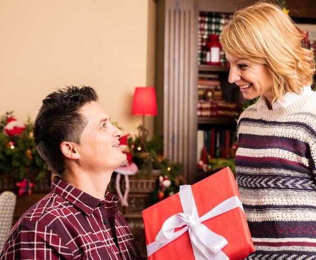 Человек сидит давая подарок своей жене