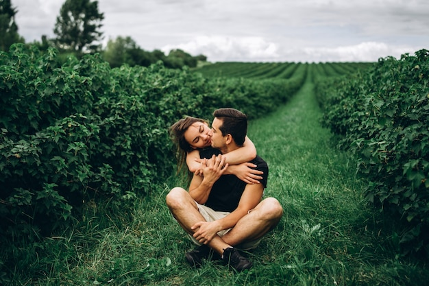 A man sitting on green grass between currant bushes, a woman with long hair hugging him from behind.