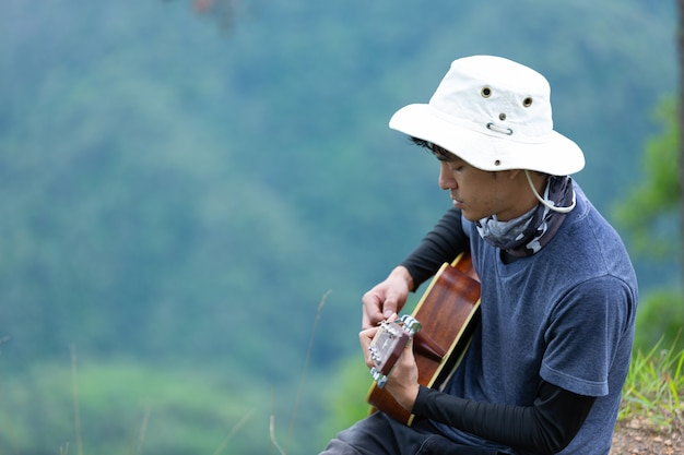 A man sitting happily playing guitar in the forest alone.