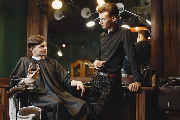 椅子に座っている男。クライアントと美容師。男はウイスキーを飲みます。