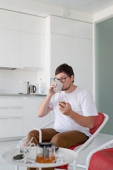 ティーカップと電話を保持しているテレビを見ている椅子に座っている男