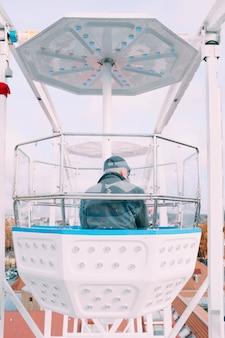 Человек сидит в кабине карусели колеса обозрения во время поездки