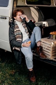Человек сидит в фургоне и пьет кофе