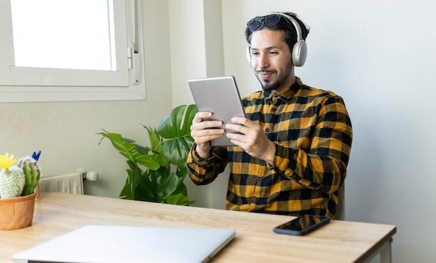 タブレットを使用してオフィスに座ってテーブルの上に座っている男性は他のラップトップです