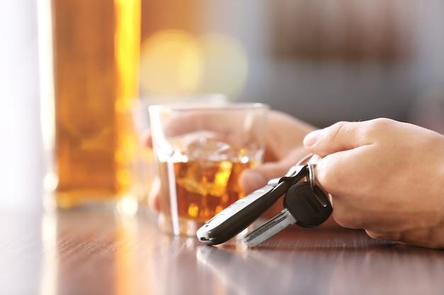 アルコール飲料と車のキー、クローズ アップでバーに座っている男。飲酒運転しないでください コンセプト