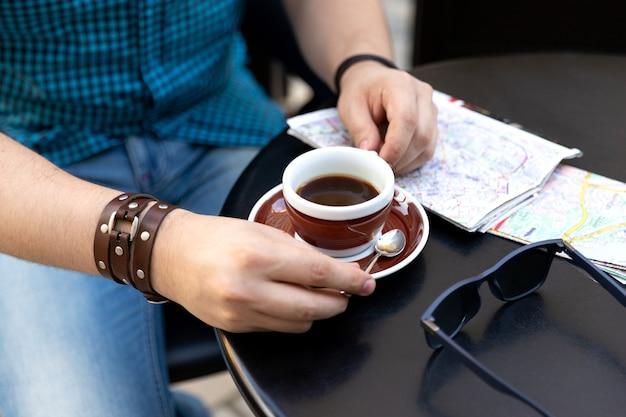 コーヒーカップと地図とカフェに座っている男