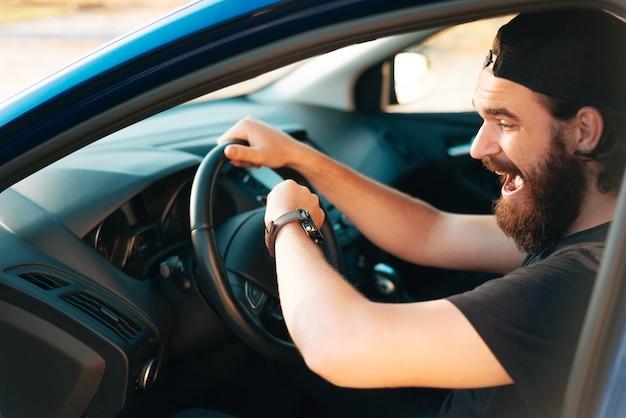 Человек сидит в карточке на рулевом колесе и потрясенно смотрит на часы, концепция задержки