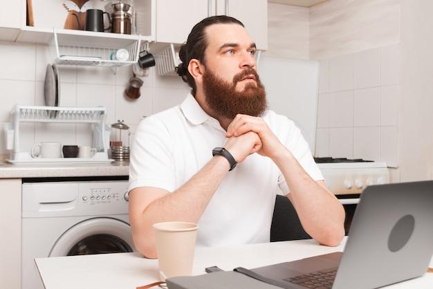 キッチンでノートパソコンの前に座って考えている男