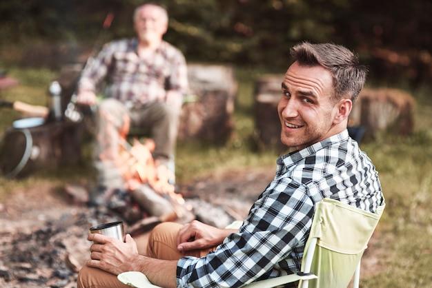 Человек сидит в своем кресле в лесу