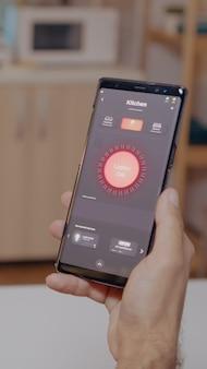 スマートフォンを保持している自動化ライトシステムで家に座っている男