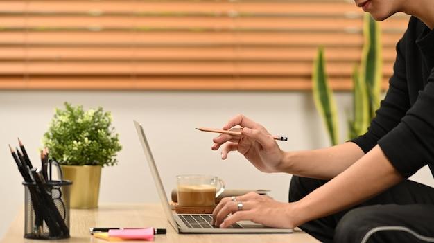 Человек сидит в гостиной и работает онлайн с портативным компьютером.