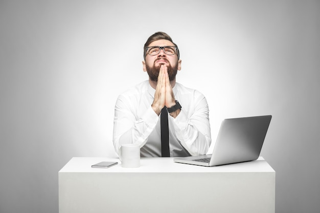オフィスに座って助けを求める男宇宙が祈るような手をつないで