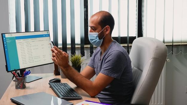 보호 마스크를 쓰고 전화를 타이핑하는 책상 위에 사무실 방에 앉아 있는 남자. 새로운 일반 작업 공간에서 일하는 프리랜서, 인터넷 기술이 적용된 휴대 전화를 사용하여 대화 쓰기