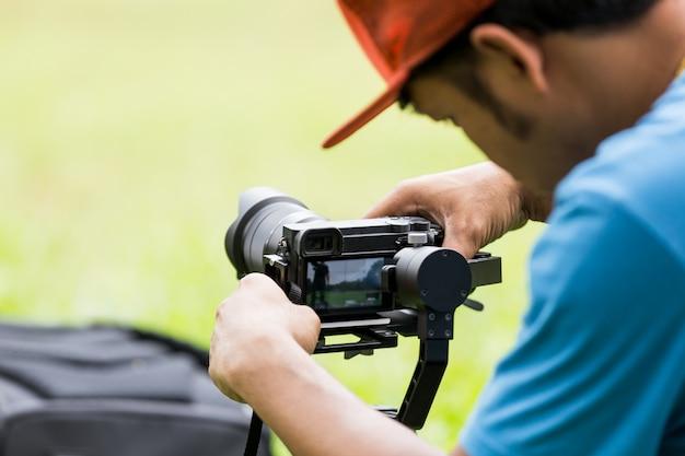 カメラの安定化モノポッドジンバルを設定して公園に座っている男