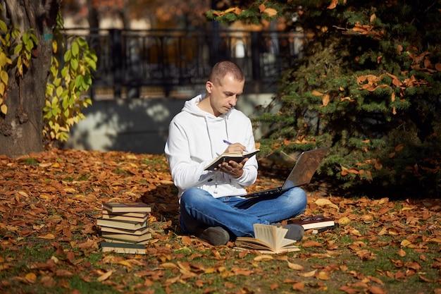 ノートパソコン、メモ帳、本、教科書を持って公園に座っている男。野外学習、社会的距離