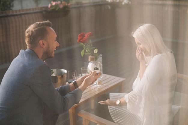 彼女のガールフレンドに婚約指輪を与えるレストランに座っている男