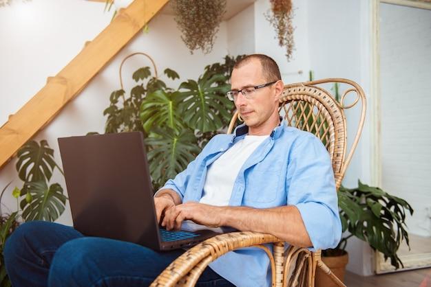 Человек, сидящий в кресле-качалке, работает с ноутбуком