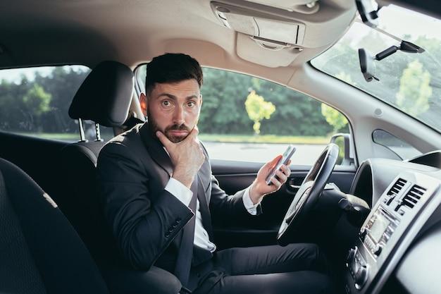 차에 앉아 전화로 뉴스를 읽고 놀란 남자