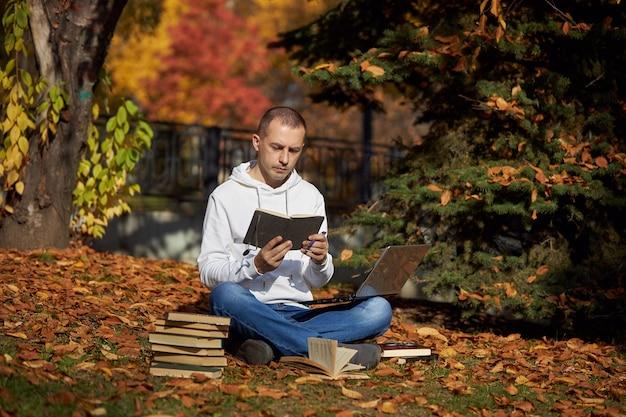 ノートパソコンと本を持って公園に座っている男