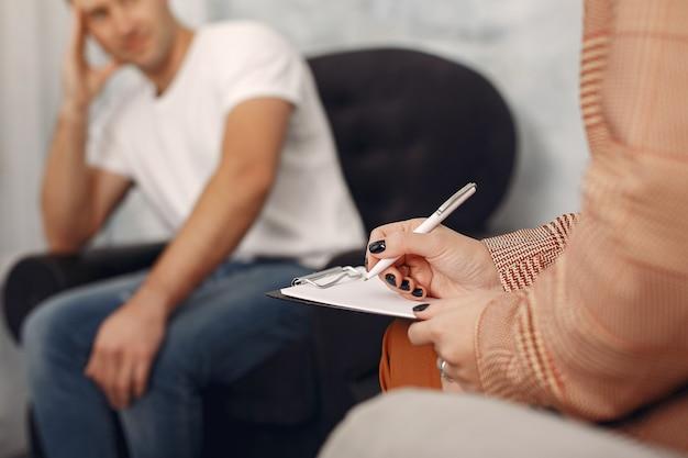 Человек сидит в кабинете психолога и говорит о проблемах