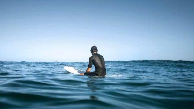 백 샷에서 물에 앉아 남자