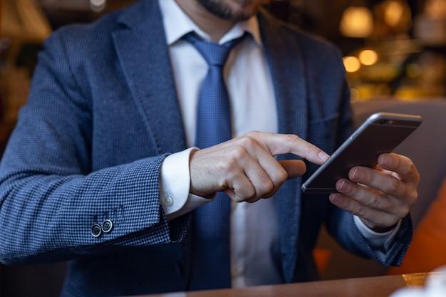 携帯電話でメッセージを書いてカフェバーの中に座っている男の人。