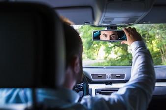 Man sitting inside car adjusting rear view mirror
