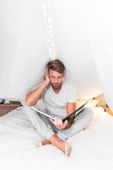 Человек, сидящий внутри занавеса, глядя на фотоальбом на кровати