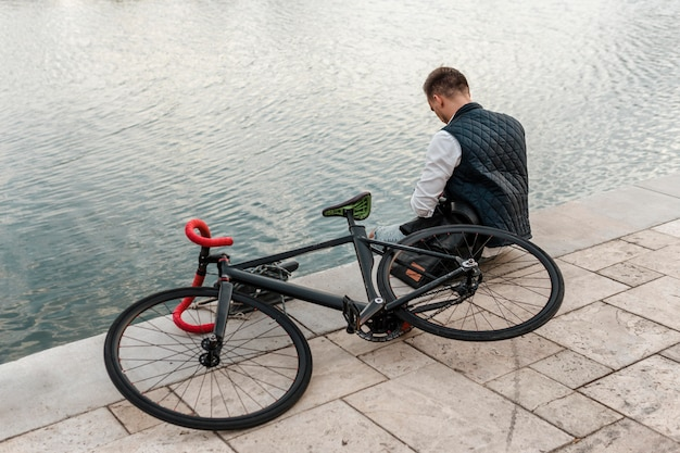 Man sitting next to a lake with his bike
