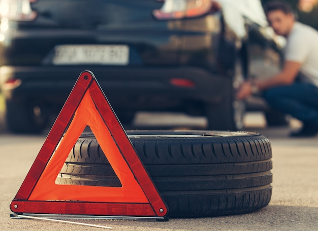 Man sitting near car with a punctured tire