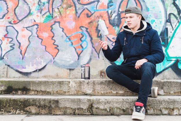 Uomo che si siede vicino al muro dei graffiti